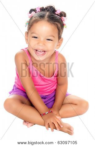 Multiracial small girl laughing with a funny expression sitting on the floor (isolated on white)