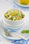 foto of devilfish  - Cuttlefish salad with fresh fava beans and corn with fresh aromatic herbs in a salad bowl of white and blue colors - JPG