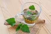 stock photo of sting  - Green stinging nettle leaves and fresh nettle tea on wooden table - JPG