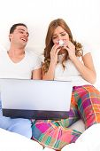 stock photo of ordinary woman  - ordinary casual young couple in love watching sad movie in bed on laptop computer - JPG