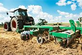 stock photo of cultivator-harrow  - Ploughing heavy tractor during cultivation agriculture works at field with plough - JPG