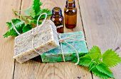 foto of nettle  - Oil in bottles two bars of homemade soap with twine nettle on the background of wooden boards - JPG