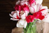 Beautiful tulips in glass jug on wooden background