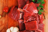 fresh uncooked beef meat slices over wooden cutting board ready to prepare with green hot and red pe