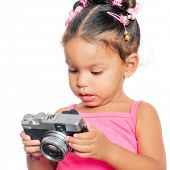 Multiracial small girl holding a compact camera isolated on white