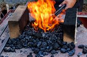 stock photo of blacksmith shop  - outdoor Old fashioned blacksmith furnace with burning coals - JPG