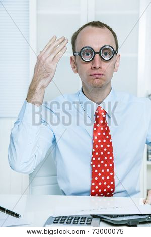 Stunned man with big glasses and a red tie at work like a comedian, bookkeeper or manager with good ideas.