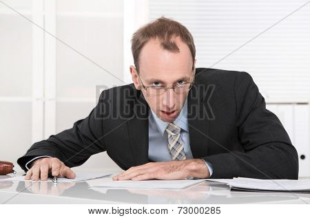 Stressed manager with crisis sitting at desk.