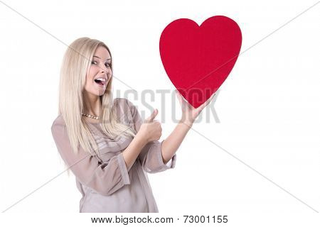 Happy young blond caucasian woman holding red heart and thump up.