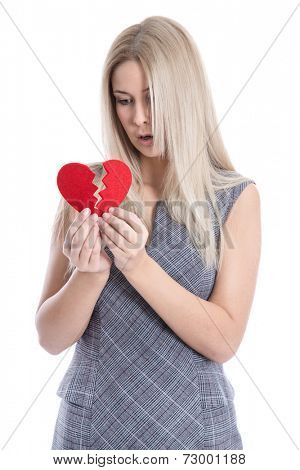 Isolated sad blond caucasian woman holding broken red heart - love sickness.