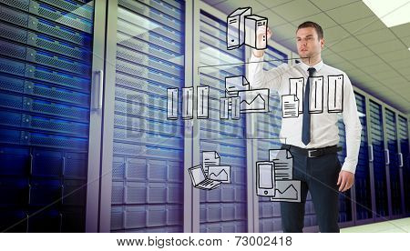Young businessman writing with marker against server room