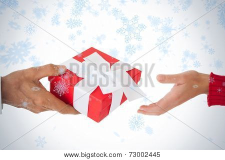 Couple passing a wrapped gift against snow falling