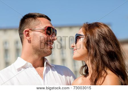 love, travel, tourism, people and friendship concept - smiling couple wearing sunglasses looking at each other in city