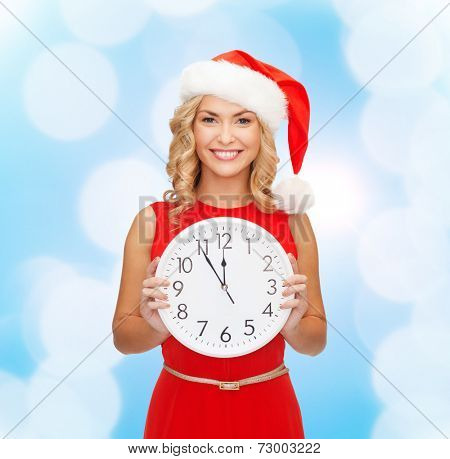 christmas, winter, holidays, time and people concept - smiling woman in santa helper hat and red dress with clock over blue lights background