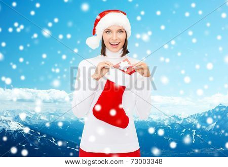christmas, winter, happiness, holidays and people concept - smiling woman in santa helper hat with small gift box and stocking over snowy mountains background