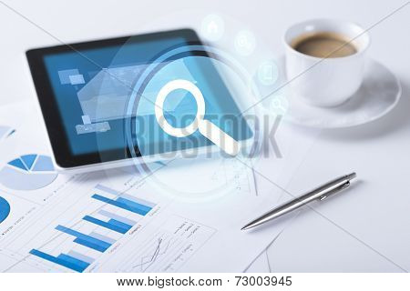 business and technology concept - tablet pc and cup of coffee with lense projection