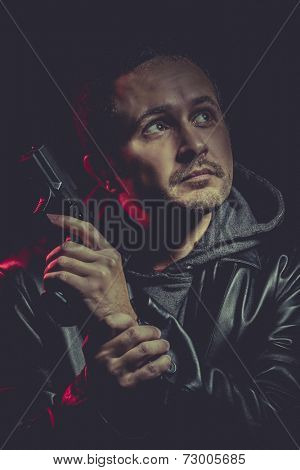 man with a gun and dressed in black leather