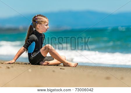 little girl sitting in a wetsuit on the beach