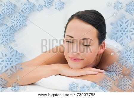 Peaceful brunette lying with salt scrub on back against snowflake frame