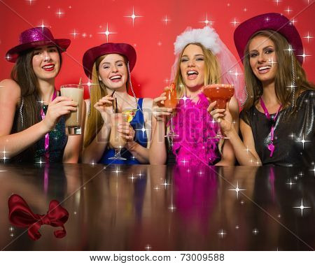 Laughing friends having hen party holding cocktails against digitally generated red shiny bow