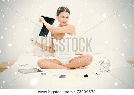 Furious young brown haired model in white pajamas throwing her laptop against snow falling
