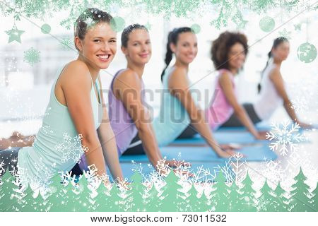 Side view portrait of a fit class doing the cobra pose against snow
