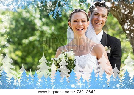 Newly wed couple with flower bouquet in park against snow