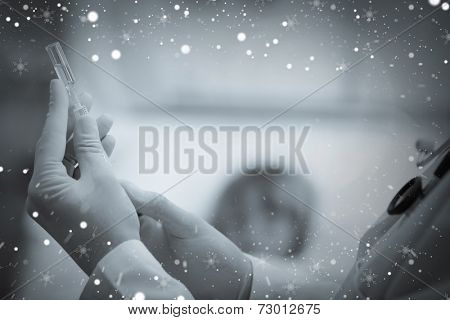 Composite image of doctor preparing a syringe against snow