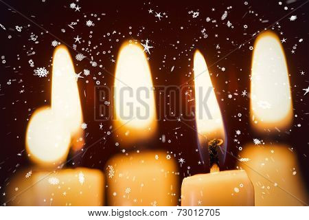 Composite image of snow falling against candles in the dark