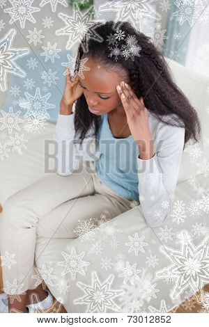 Composite image of Woman with headache sitting on sofa against snowflakes on silver