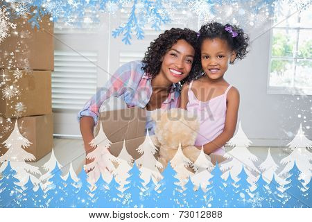 Cute daughter unpacking her teddy bear with mother against snow