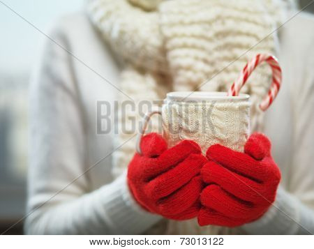 Woman holding winter cup close up on light background. Woman hands in woolen red gloves holding a cozy mug with hot cocoa, tea or coffee and a candy cane. Winter and Christmas time concept.