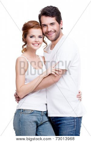Beautiful happy young couple dressed in blue jeans and white undershirt - isolated on white background.