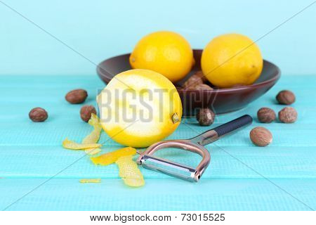Ripe lemons and nutmegs on plate and half peeled lemon with peeling knife on blue wooden background
