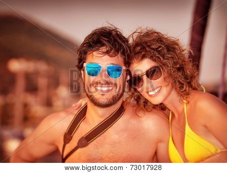 Closeup portrait of attractive young couple on the yacht in sunset light, luxury lifestyle, happy tourists on summer vacation on the sea