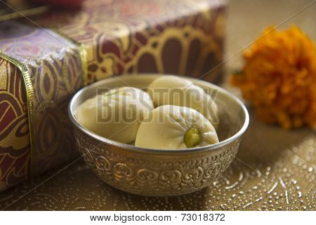 A bowl of an Indian sweet along with gift box in the background