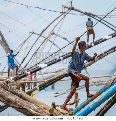 FORT KOCHI, INDIA - FEBRUARY 15: fishermen operate a Chinese fishing net based on ancient technology and traditional materials, ropes and stones on February 15, 2013 in Fort Kochi, Kerala, India.