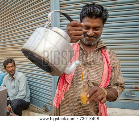 MYSORE, INDIA - FEBRUARY 8, 2013 - Men pours cup hot milk tea Indian style or chai for customers from his shop along street