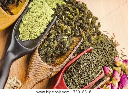 dry tea in scoops close up on wooden table background top view