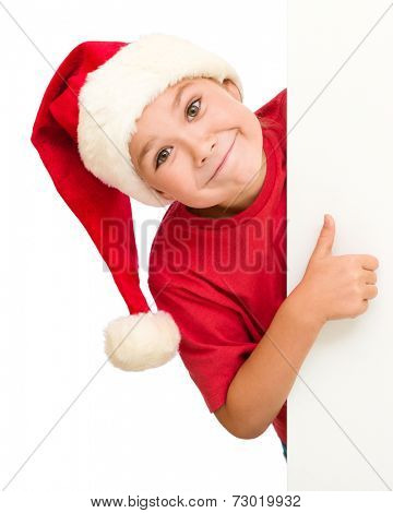Little girl in santa hat is holding blank board and showing thumb up sign, isolated over white