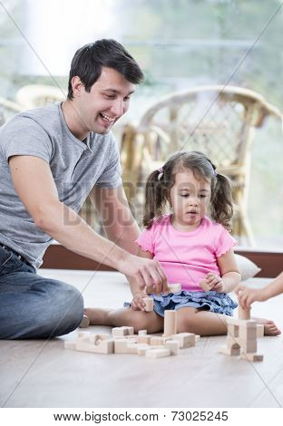 Portrait of happy father and daughters playing with abacus in house