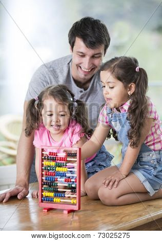 Happy father and daughters playing with abacus in house