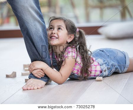 Low section of father dragging girl on hardwood floor