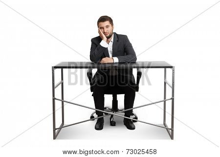 wearied businessman sitting at table and looking at camera. isolated on white background