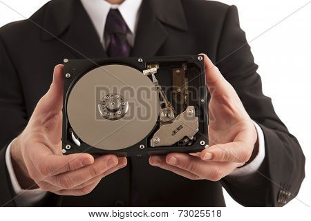 Close-up of businessman showing physical parts of hard drive on white background