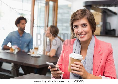 Pretty brunette sending a text drinking coffee at the coffee shop