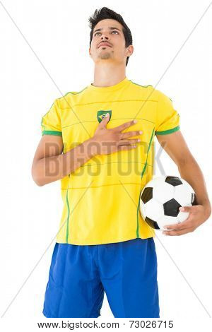 Brazilian football player in yellow listening to anthem over white background