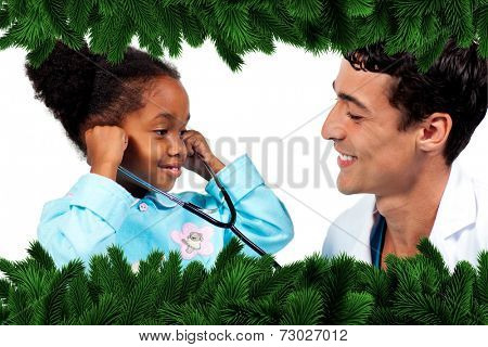 Smiling doctor and his patient playing with a stethoscope against fir tree branches forming frame