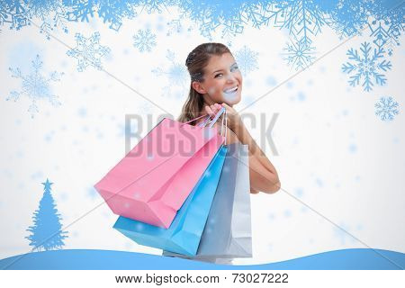 Back view of a cheerful woman holding shopping bags against snow flake frame in blue