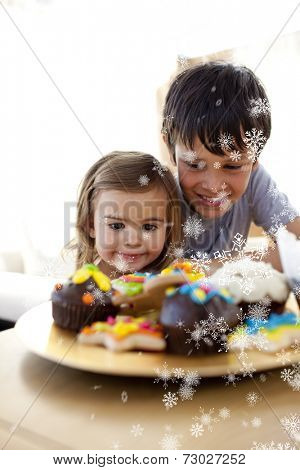 Composite image of Brother and sister looking at confectionery with snow falling
